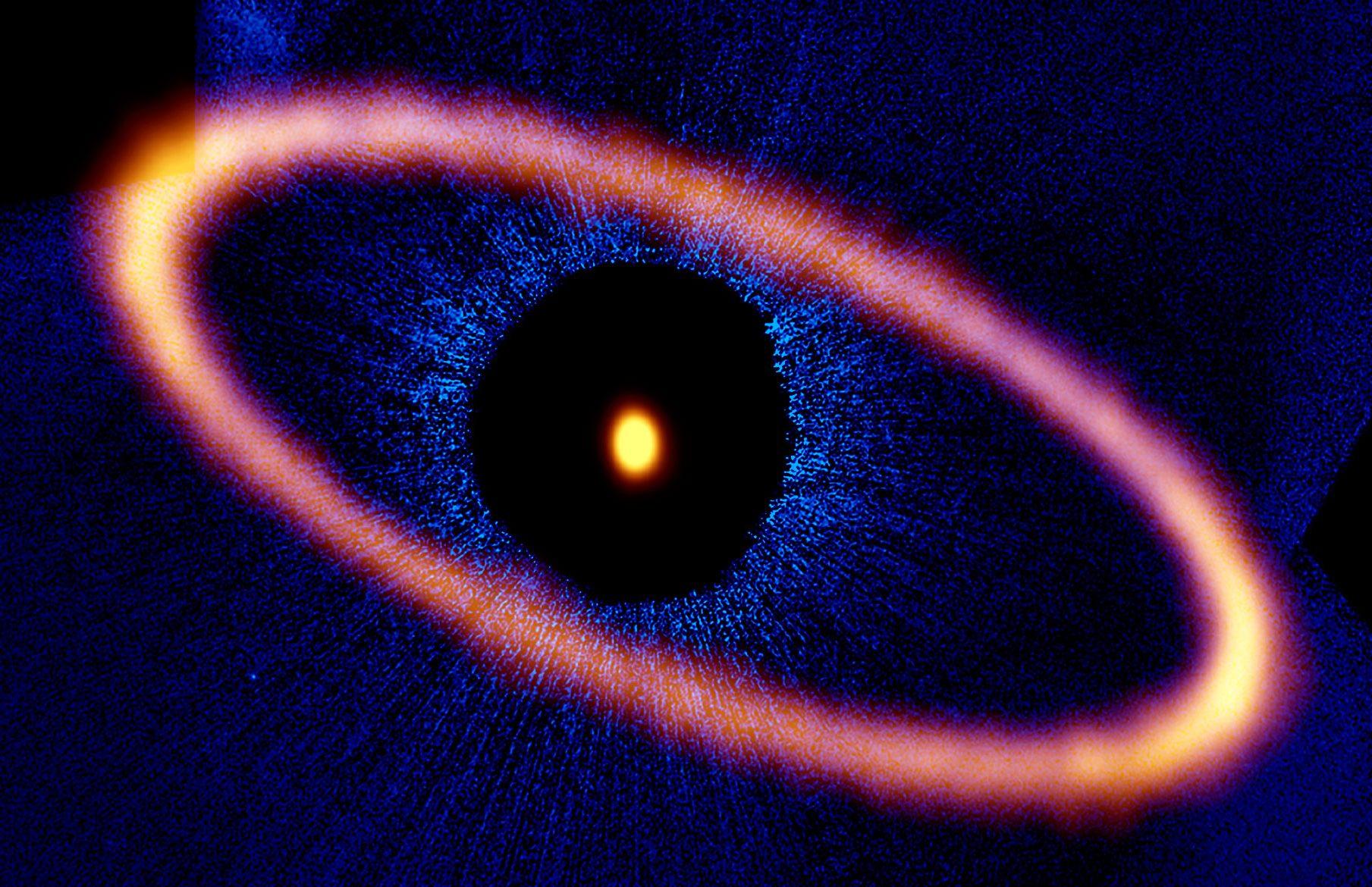 アルマ望遠鏡(オレンジ)とハッブル宇宙望遠鏡(青)で撮影したフォーマルハウトを取り巻く環。アルマ望遠鏡でもフォーマルハウト本体から発せられる電波が検出されています。ハッブル宇宙望遠鏡の可視光写真では、星のまわりを鮮明に写し出すために、「コロナグラフ」を使って星の光を隠しています。 Credit: ALMA (ESO/NAOJ/NRAO), M. MacGregor; NASA/ESA Hubble, P. Kalas; B. Saxton (NRAO/AUI/NSF)