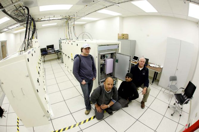Hydrogen maser atomic clock installed at the ALMA Array Operations Site (AOS), along with the technicians who installed it.