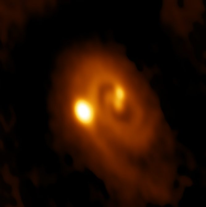 ALMA image of the L1448 IRS3B system, with two young stars at the center and a third distant from them.